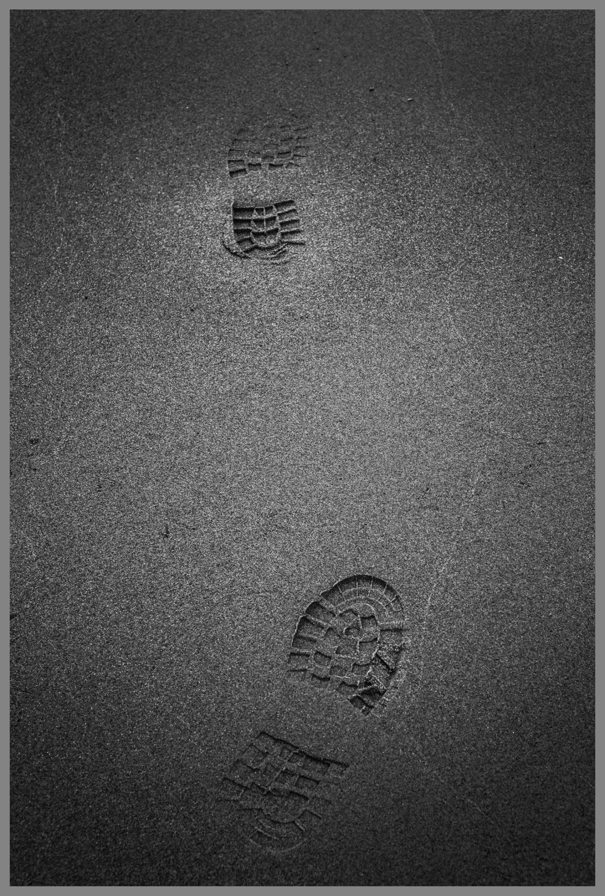 Schwarzweiße Fußabdrücke im Sand